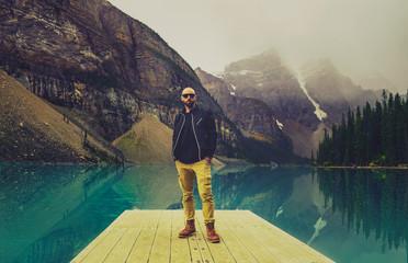 Man On Dock At Pristine Mountain Lake In Wild Adventure Explore