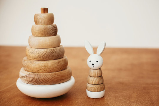 Stylish wooden toys for child on wooden table. Modern simple wooden pyramid with rings and bunny. Eco friendly, plastic free educational toys for toddler