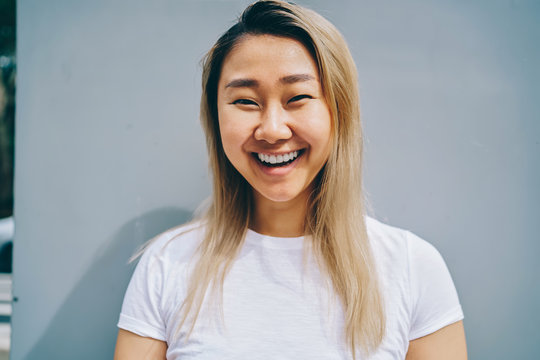 Half length portrait of cute asian girl having fun during free time laughing posing on blue background, cheerful blonde asian woman in shirt with copy space for brand name or label looking at camera