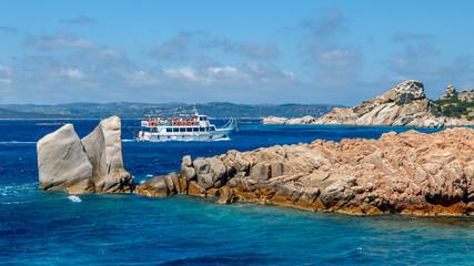 Cruise boat with tourists in the sea near rocky coast of Sardinia, the Maddalena archipelago.