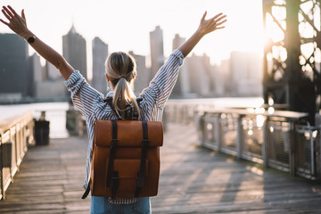 Back view of accomplished tourist woman with trendy backpack and raised hands celebrating win with trip to American city - New York, female traveller complete triumph and win goal during journey