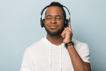 Calm African American man in headphones enjoying favorite music