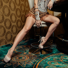 Long female legs in burlesque clothes and high heels shoes on tall leather chair near bar table