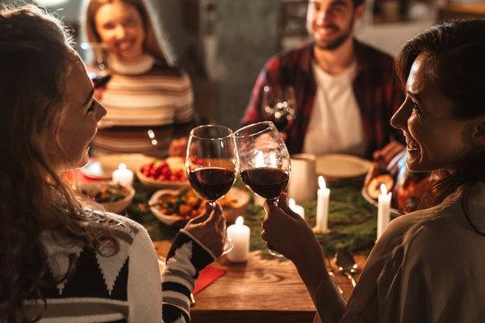 Photo of nice joyful people drinking wine and having Christmas dinner