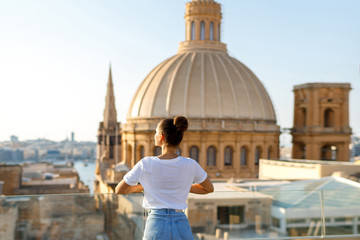 Obraz A brunette woman stands on a balcony at a height against the background of the city and the church with a dome. Focus on the woman. Back view - fototapety do salonu