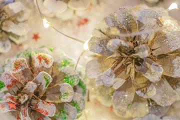 Pomme de pin décorée et peinte avec des paillettes et des guirlandes lumineuses pour les fêtes de fin d'année Noël et nouvel an pour décorer la table des réveillons