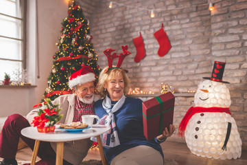 Senior couple exchanging presents on Christmas day