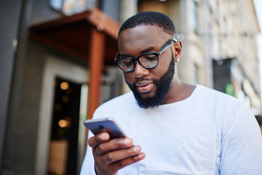 Millennial dark skinned man using smartphone app for booking online while spending time outdoors, african american hipster guy in optical spectacles read notification from chat on mobile phone
