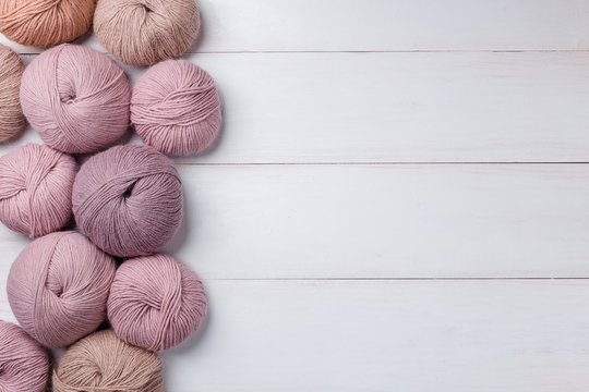 Woolen skeins of thread on white boards. ball of thread from Italian Angora. A knitting project is underway. A piece of knitting with a ball of yarn and knitting needles.