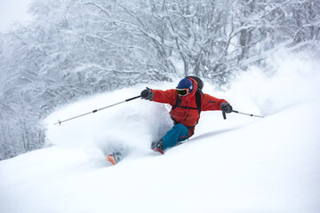 Fototapete - A skier is in the deep snow.