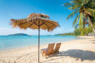 Beach Chairs and Umbrella on summer island with clear water sea and wave with speed boat in background in Phuket, Thailand. Summer, Travel, Vacation and Holiday concept.