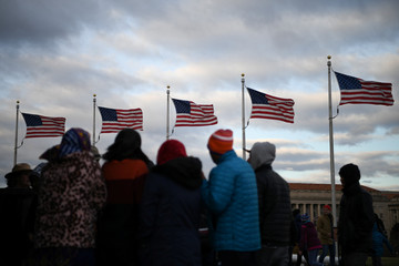 American flags wave in the wind behind tourists standing in line at the base of the Washington Monument in Washington
