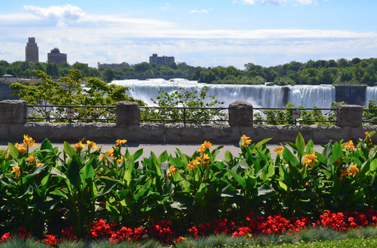 contrast of a beautiful garden facing Niagara Falls from the Canadian side and the view of the USA in the background