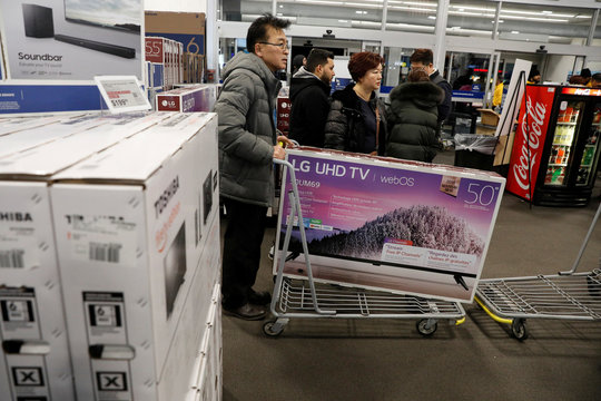 People shop for televisions at Best Buy during a sales event on Thanksgiving day in Westbury, New York
