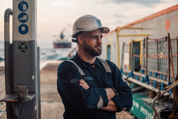 Marine Deck Officer or Chief mate on deck of offshore vessel or ship , wearing PPE personal protective equipment - helmet, coverall