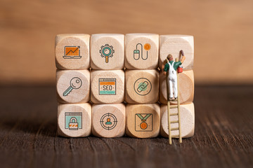 little painter figure is writing marketing symbols on wooden blocks