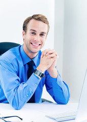 Portrait of young happy smiling confident businessman in blue shirt and tie at workplace. Success in business, job and education concept shot.