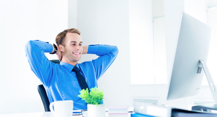 Happy smiling relaxing or dreaming confident businessman in blue shirt and tie, with hands behind head, using desktop computer at office. Success in business, job and education concept.