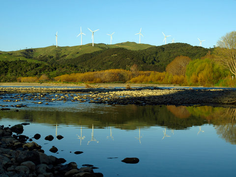 scenic view of wind turbine farm on a mountain range from a river