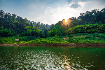 take a boat to beautiful blue sky green forest mountains lake view at Khun Dan Prakarn Chon Dam waterfall,  nakhon nayok, Thailand. an idea for backpacker hiking or camping on long weekend holiday