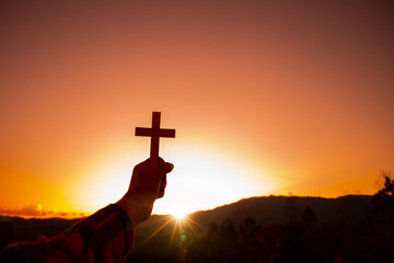 Human hand holding cross with a sunset sky background. Christian silhouette concept.