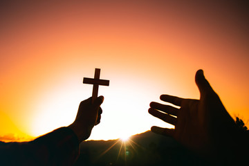 Human hand holding christian cross and praying with a sunset sky background. Christian silhouette concept.