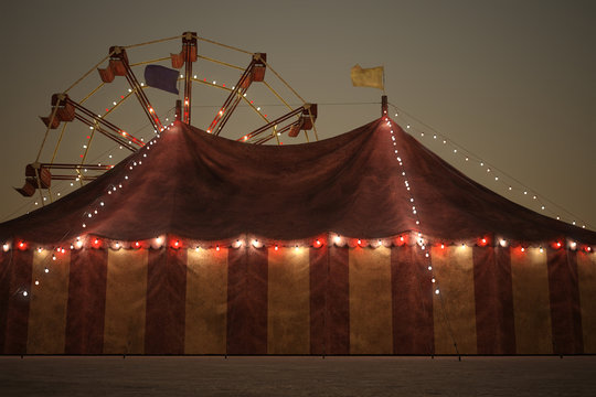 Beautiful night time carnival image of a big top tent and a ferris wheel in the background.