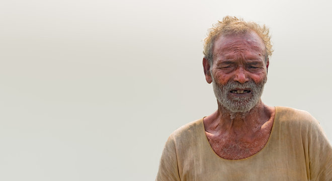 Portrait of poverty stricken Old Aged Male of South Asian origin in his late 70s, posing in dubious mood. Belongs to labour class, is tired and wearing pale and dirty stinky clothes, have white beard