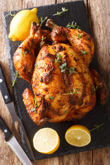 In de dag Kip Freshly cooked rotisserie chicken with ginger and spices close-up on a slate board. Vertical top view
