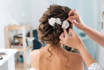 Poster Kapsalon hairdresser makes an elegant hairstyle styling bride with white flowers in her hair