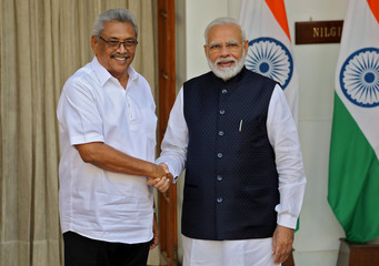 Sri Lanka's President Rajapaksa and India's PM Modi shake their hands during a photo opportunity ahead of their meeting at Hyderabad House in New Delhi