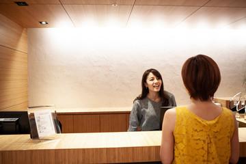 カウンターで来訪者の案内をする女性