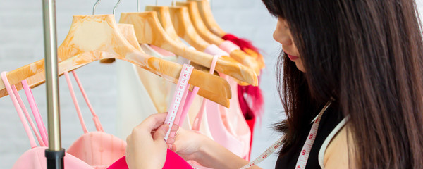 Pensive adult Asian seamstress focusing and checking details with measuring tape while making dress collection in contemporary sewing workshop against blurred white wall