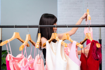 Gladful Asian female holding hanger and touching elegant red dress while standing beside rack and examining clothes collection in showroom