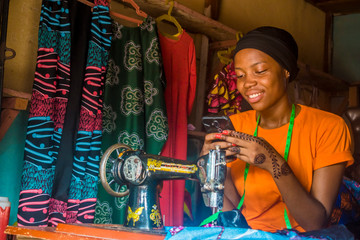 Obraz young african woman who is a tailor smiling while using her mobile phone - fototapety do salonu