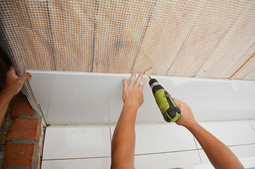 Decorative PVC ceiling panels installation. Contractors installing white PVC Ceiling Boards with screw gun in the house bathroom