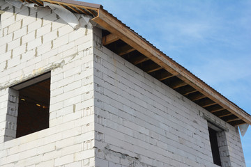 House under construction with unfinished roof fascia boards and with no soffit panels