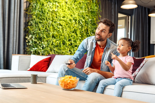 Mixed Race Family. Father and daughter sitting on sofa at home watching cartoon on tv together eating snacks smiling curious