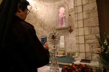 A worshipper photographs a fragment of a wooden relic in Jerusalem's Notre Dame