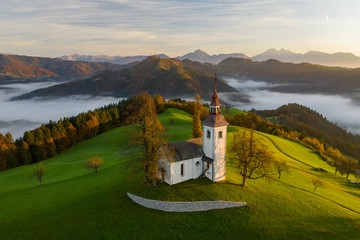 Aerial view of the hills, colorful forest in the fog and the church of Sv Tomaz. Sunrise in Slovenia in autumn