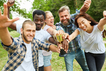 Gruppe junger Leute mit Pokal jubelt