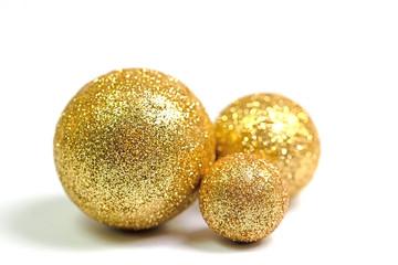 Drei goldene Kugeln vor weißem Hintergrund