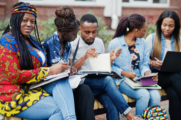 Group of five african college students spending time together on campus at university yard. Black afro friends studying at bench with school items, laptops notebooks.