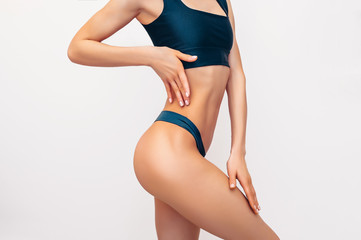 Unrecognizable fit woman in black lingerie on white background isolated. Muscular slim attractive female with flat belly. Copy space for text. Body care, healthy and sporty life, hair removal concept