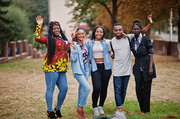 Row of group five african college students spending time together on campus at university yard....