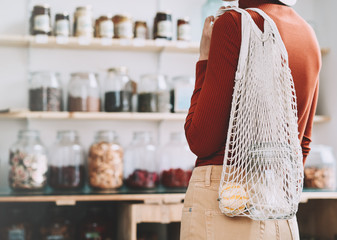 Young woman in zero waste shop or plastic free store.