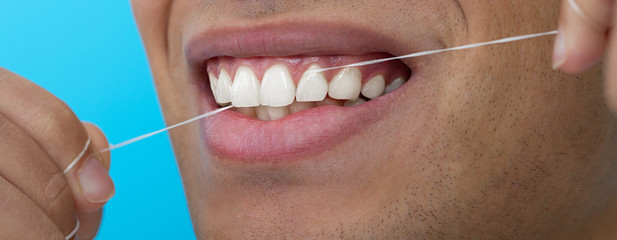 Close-up male mouth while flossing teeth with dental floss on blue background. Dental hygiene