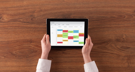 Hand holding tablet with timetable and calendar concept