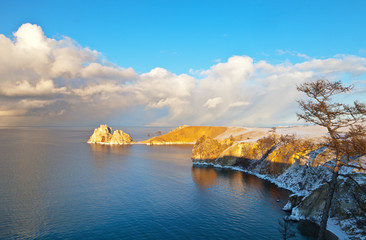 Baikal Lake in December. Olkhon Island and the Small Sea Strait in sunset light. View of the famous Shamanka Rock - a natural landmark of the lake. Beautiful tranquil landscape