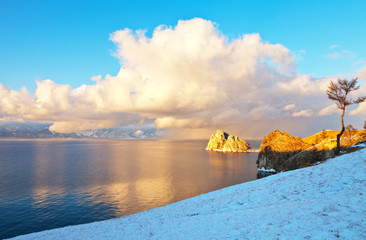 Baikal Lake in December evening. Snowy clouds above the Small Sea Strait. Shamanka Rock - famous natural landmark of Olkhon Island at sunset. Beautiful calm landscape. Winter background